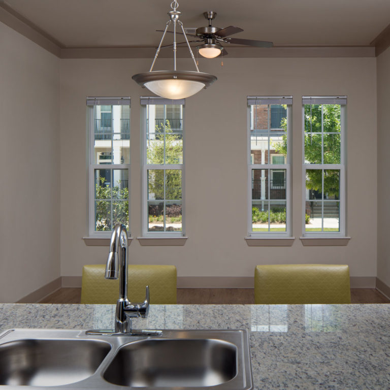 Interior view of kitchen and living area at Heritage Senior Residences at Columbia Parc - New Orleans, LA